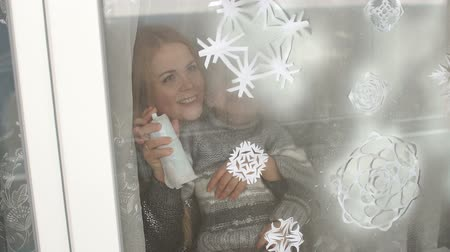 samolepky : Mom and her son decorate the windows for Christmas with snowflakes and artificial snow, they spray artificial snow on paper snowflakes on the window.