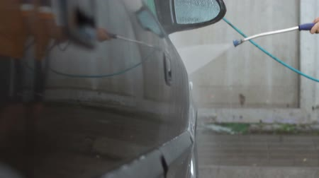 lavagem : Close-up of a young man washes his car on a wash self-service. Car at the car wash cleaned to a shine.