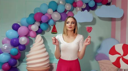 кукла : A young girl in bright clothes with lollipops in her hands in a studio with balloons, marshmallows and ice cream, she can not choose one lollipop of two.  Candy girl. Стоковые видеозаписи
