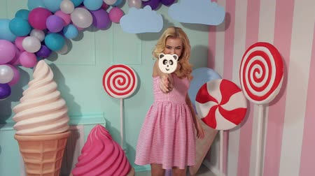 lollipop : Portrait of a cheerful and happy girl in a pink striped dress with a large candy in the form of a panda on the background of colorful balloons, a large plastic ice cream and candy. Stock Footage