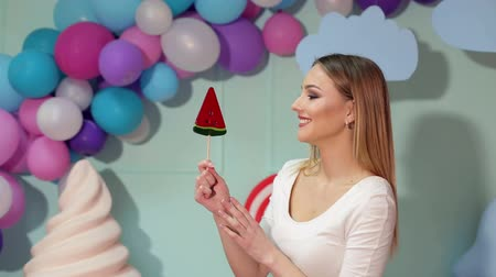 infantil : A young laughing girl holds a big candy in her hands and looks at her greedily against the background of colorful balloons in a bright studio. Vídeos