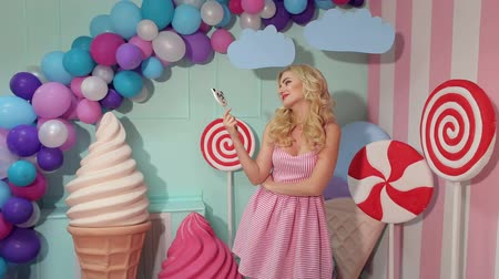 lollipop : Portrait of a cute girl with blond curly hair in a pink dress and a big candy in her hands at a candy party. Stock Footage