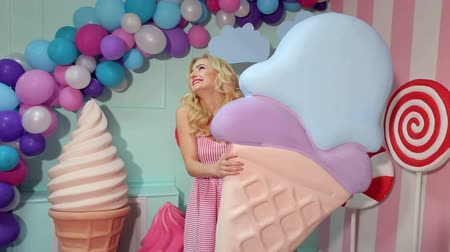 lollipop : A charming girl in a pink dress with long blond hair is holding a huge colorful ice cream in the studio decorated with a bunch of different sweets. Candy girl.