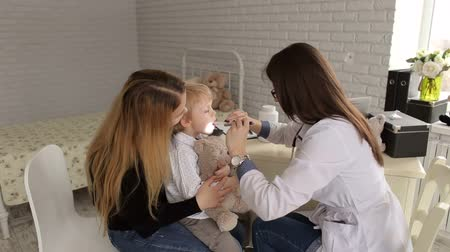 pediatria : A girl doctor examines the throat and mouth to a small child with a flashlight and a spatula, a small boy is sitting on his mothers arms and holding a teddy bear. Pediatrics. Wideo