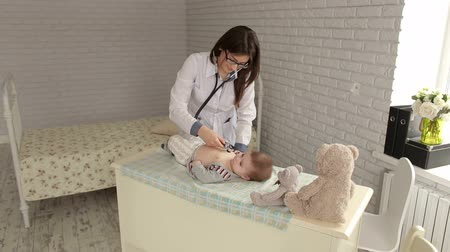 examining : Pediatric doctor exams newborn baby boy with stethoscope in hospital. Doctor checking a babys heartbeat with a stethoscope, next to the baby lies a Teddy bear.
