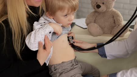 physicians : The doctor listens to the lungs and the heart with a stethoscope to a small boy in a childrens hospital, the child is sitting in the arms of his mother. Stock Footage