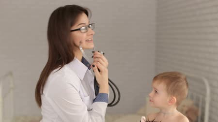 kaszel : Kind woman doctor examines a young child with a stethoscope in a modern clinic, the boy is holding a toy. Close-up of a child on examination by a pediatrician.