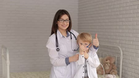 inhalacja : Pediatrics doctor hold a mask vapor inhaler to a little boy breathing through a steam nebulizer. The doctor and the child with inhalation mask showing thumb up, portrait. Wideo
