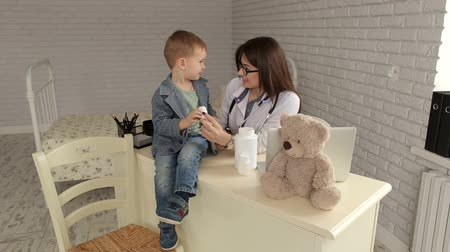 плюшевый мишка : Beautiful smiling female doctor hold in arms pill bottle and shows it to the child, close-up. Cute good doctor pediatrician talking with a young boy in the clinic.