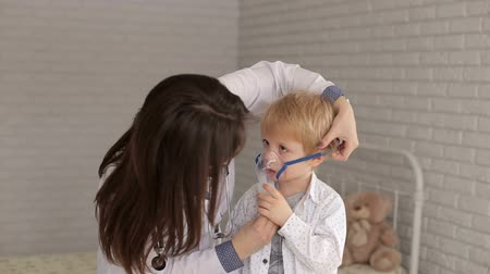 lung : A woman pediatrician puts on an inhaler mask to a young boy in the hospital.