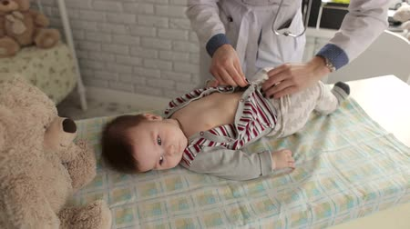 vyšetření : Female doctor undresses a newborn baby for a checkup at the clinic. The childrens pediatrician. The family doctor examines a newborn baby at home. Dostupné videozáznamy