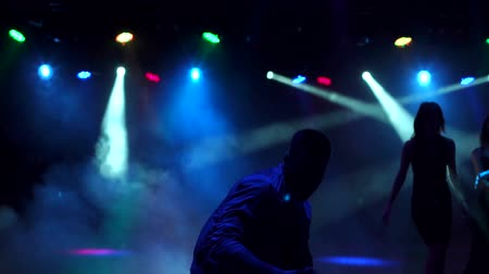 félrebeszél : Silhouette of young guy dancing in a nightclub, in the background dancing young girls. Night party. A group of young people dancing and having fun in the dark on the background of flashing lights. Stock mozgókép