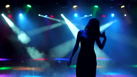 bachelorette party : Cute beautiful brunette in evening dress dancing at a bachelorette party on the background of bright spotlights. Silhouette. Slow motion. Stock Footage