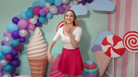 pinup : Portrait of a cheerful dancing girl in a pink skirt and white blouse on the background of the interior with big sweets- candy, she pretends to dive underwater with her nose closed. Stock Footage