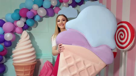 леденец : A cute happy girl holds a giant plastic ice cream in her hands offering it to you. Cute style. The girl is a sweet tooth. Sweet shop. Стоковые видеозаписи