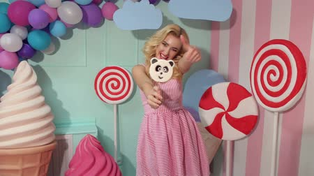 панда : Portrait of a cheerful girl with a large candy in the form of a panda on the background of colorful balloons, a large plastic ice cream and candy, she points her finger at the candy.