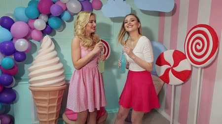леденец : Happy laughing girls in colorful bright clothes drink a cocktail of glass bottles against the background of colorful balloons and giant ice cream.