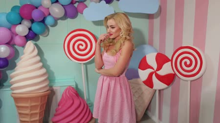 pinup : Portrait of a cheerful girl in a pink striped dress and hairstyle on the background of the interior with big sweets- candy, marshmallows and balloons. Girl posing for camera in Studio with sweets.