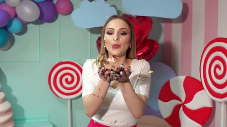 słodycze : Charming happy girl blowing on confetti on bright colorful background with huge lollipops, ice cream and marshmallows, slow motion. Bachelorette. Wideo