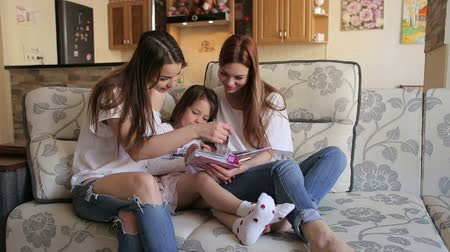photo album : Three sister, two adults and one a small, look photo album sitting on couch. A young mother with a small daughter and an older sister watching a photo album at home on the couch.