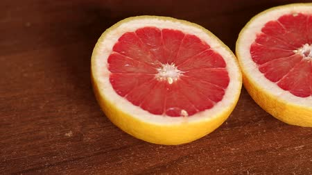 grejpfrut : Cut grapefruit on a wooden table. Fresh grapefruits on wooden background. Citrus. Background. Slow camera movement from left to right.