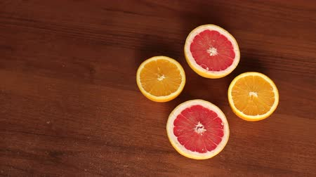 segmento : Four halves of juicy orange and grapefruit on a wooden brown background. Sliced oranges and grapefruit on wooden table. Close-up. Slow motion. The view from the top.