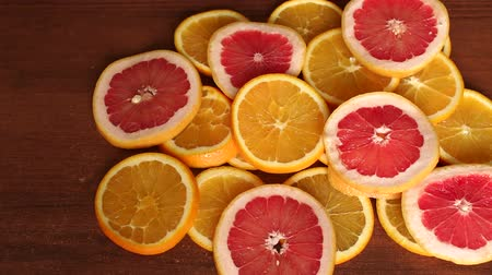 цитрусовые : Sliced citrus fruits, oranges and grapefruit, on wooden table, close-up. Abstract background with citrus-fruit of orange slices. Close-up. Sliced orange background.