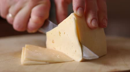 фета : Close-up of female cook or housewife cutting cheese with a knife, slow motion.