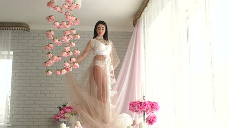 naga : Sexy and beautiful young girl in a bridal underwear and transparent fluffy dress in boudoir in the morning. Wideo