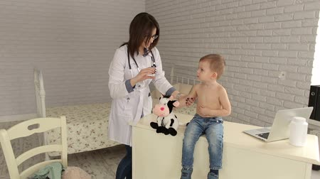 иммунизация : Doctor pediatrician plays before the injection with the boy. A woman doctor shows a little boy a syringe, they play with a syringe before injection. Стоковые видеозаписи