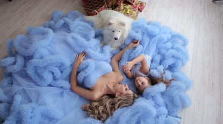 samoyed : Young woman and little girl in the same fluffy dresses lying on the floor with the dog posing for the camera. Dog husky Samoyed. Stock Footage