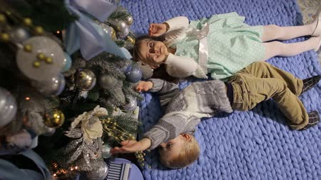 клетчатый : Two small children lie on the floor and look at the Christmas tree from the bottom up.
