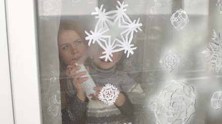 autocolantes : Mom and her son decorate the windows for Christmas with snowflakes and artificial snow, they spray artificial snow on paper snowflakes on the window.