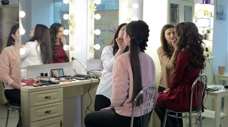 ábrázat : Group of make-up artists working with models in the beauty salon. Two make-up artists doing makeup for two models in the beauty salon.