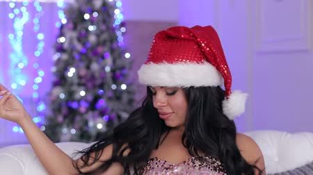 каблуки : The beautiful brunette in a brilliant evening dress and Santas red hat sits on a sofa near a Christmas fir-tree.