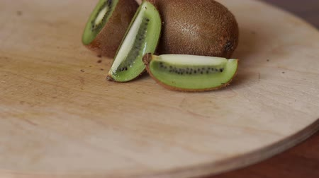 kivi : Ripe juicy sliced fruit kiwi on a wooden table in the kitchen, close-up. Slow motion.