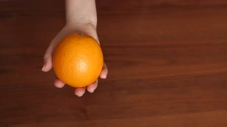 citrusové plody : Close-up of a girl holding a juicy ripe orange on brown wooden background. Slow motion.
