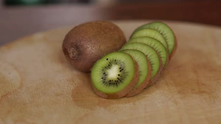 yarım uzunluk : Close-up of ripe sliced kiwi on wooden background. Ripe sliced kiwi on cutting Board, Slow motion.