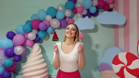 кукла : A cheerful girl with big lollipops in her hands is having fun in a bright room with balloons and a large plastic ice cream. Candy girl.