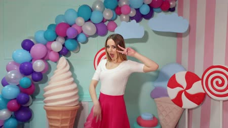 pinup : Portrait of a cheerful dancing girl in a pink skirt and white blouse on the background of the interior with big sweets- candy.
