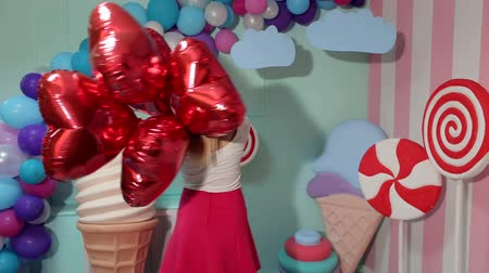 леденец : Portrait of a young beautiful girl with red balloons in the shape of a heart on a bright background with huge sweets.