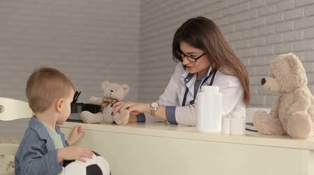 consulting : Lovely woman doctor talking with a little boy in the office. Pediatrics. A small child at a doctors appointment. The doctor is playing with a little boy Teddy bear. Stock Footage