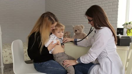 health insurance : The doctor listens to the lungs and the heart with a stethoscope to a small boy in a childrens hospital, the child is sitting in the arms of his mother. Stock Footage