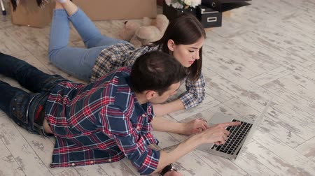 belongings : A happy couple in plaid shirts lay on the floor in a new apartment with a laptop. Young couple with laptop on the floor in a new house. Close-up. Rear view.