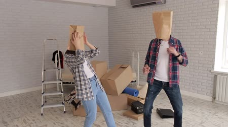 caráter : Portrait of cheerful young people who put on their heads paper bags, housewarming. A happy couple is having fun in their new apartment with cardboard packages on their heads.
