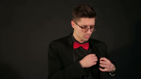 to you : Handsome young man showing middle finger, insult sign on black background. Fashionable guy in glasses, a black jacket and a red bow tie shows the middle finger taking his hand out of the jacket pocket