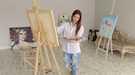 разорвал : Young beautiful girl with long hair is holding a palette with paints and draws a picture on canvas, close-up.