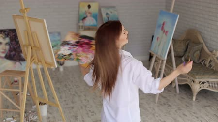 realization : A happy creative girl artist in a white shirt and jeans spinning around herself in a studio among many paintings. Young artist painting in the house. Art.