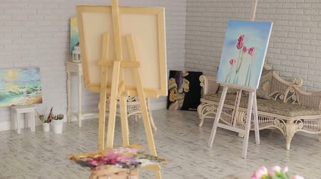 palette knife : Interior of a painters studio or gallery with colorful canvases. Painting studio interior. Easel, chair, colors and paintings all around. Stock Footage
