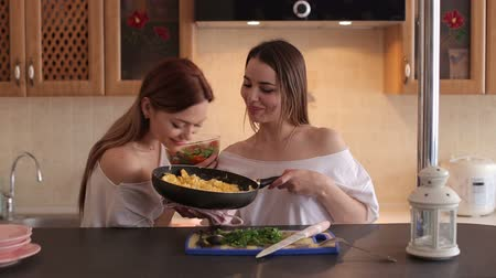 lesbijki : Two loving girls prepare Breakfast at home in the kitchen, they fry eggs in a pan. Twin sisters make an omelet in the kitchen.
